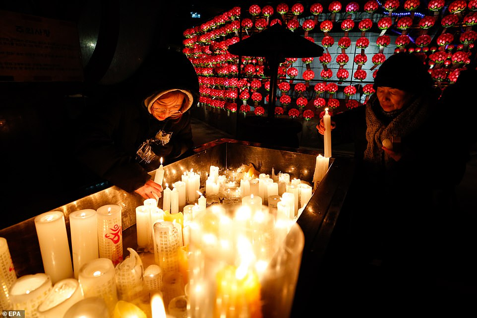 South Korean Buddhist devotees light candles as they pray at the Jogyesa temple on New Year's Eve in Seoul