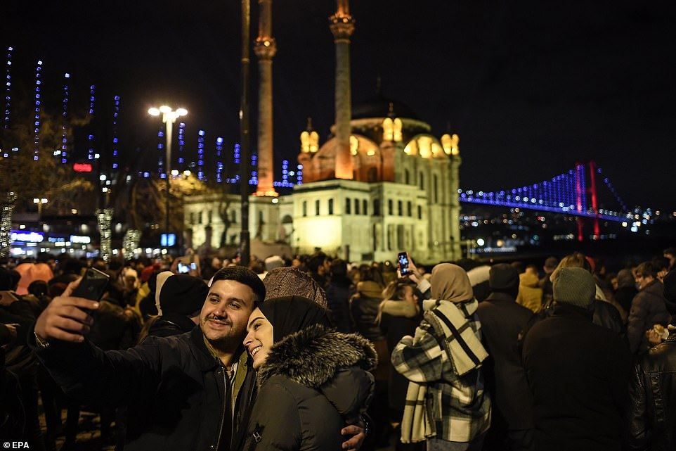 People celebrate the turn of the year in front of the Ortakoy mosque and 15 July Martyrs Bridge near the Bosphorus during new year's celebrations in Istanbul, Turkey, 01 January, 2020