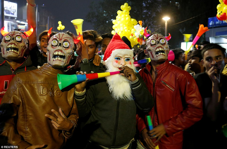 People wearing masks blow horns during celebrations to welcome the New Year in a road in Ahmedabad, India, December 31, 2019
