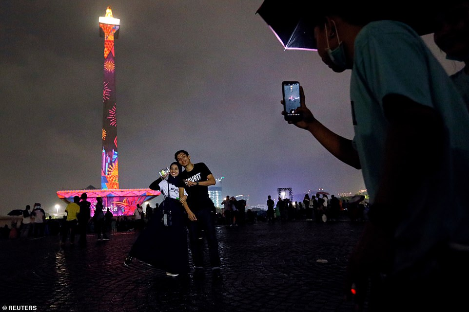 A couple takes pictures as National Monument (Monas) is illuminated by video mapping during New Year's Eve celebrations in Jakarta
