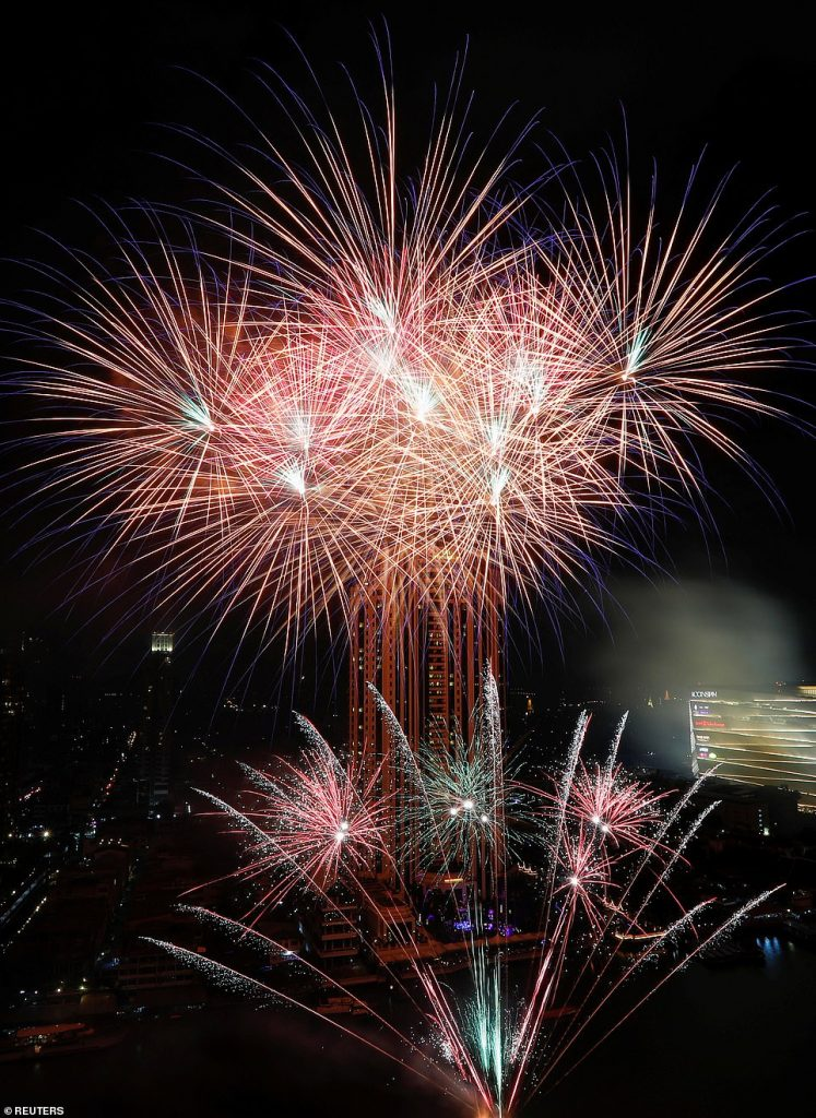 Fireworks explode over Chao Phraya River during the New Year's celebrations in Bangkok, Thailand