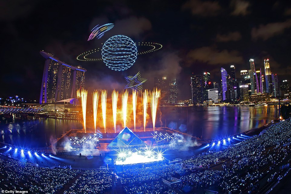 Drones are seen in the sky forming the shape of a planet as Singapore awaits 2020 with curtain-raiser fireworks by Star Island as revellers join in the biggest countdown celebration at Marina Bay on December 31, 2019