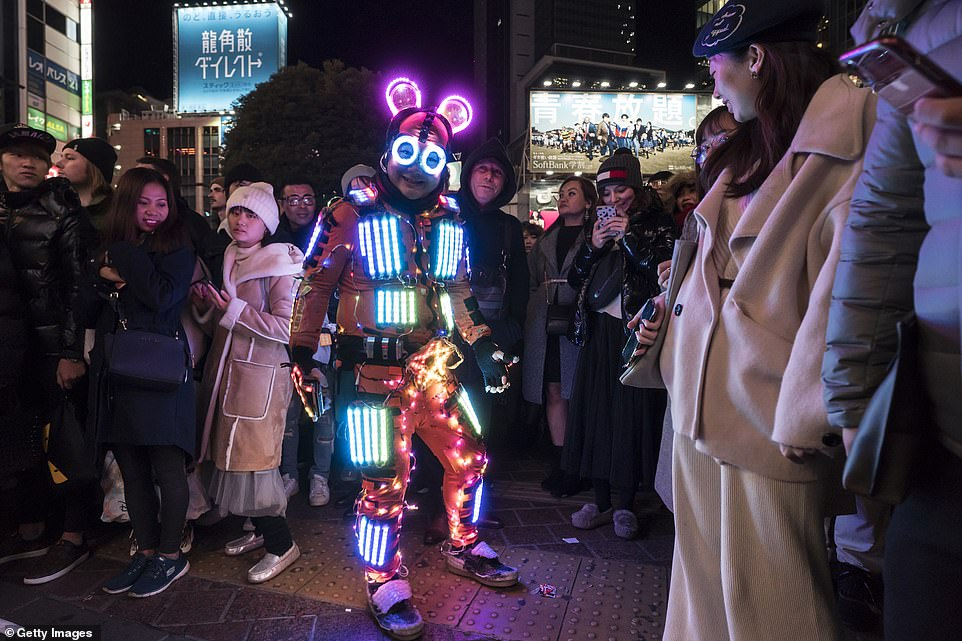 A man wearing a costume with LED lights poses for a photograph during the You Make Shibuya Countdown 2019-2020 event at Shibuya Crossing in Tokyo today