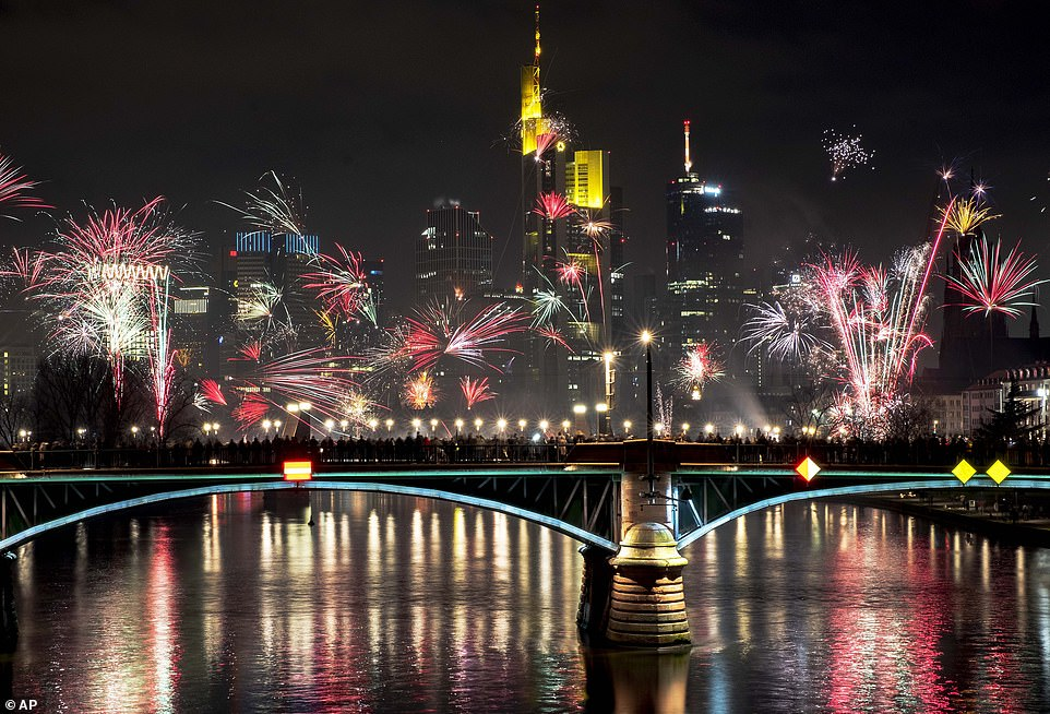 People stand on a bridge and watch fireworks during New Year celebrations near the buildings of the banking district in Frankfurt, Germany, late Wednesday, January 1, 2020