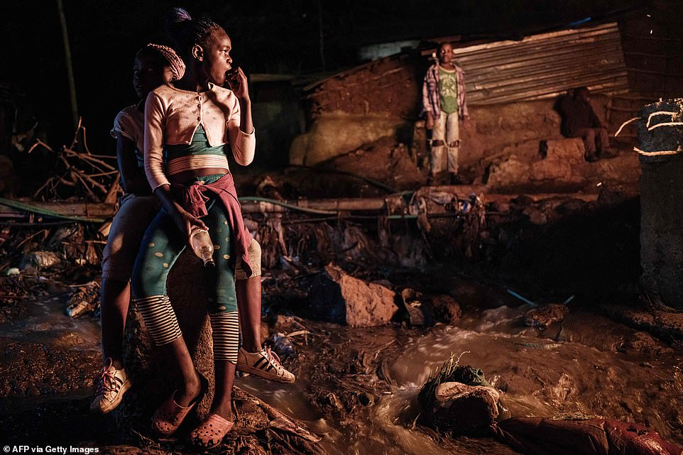 Girls look at burning tires to celebrate the new year at the Kibera slum in Nairobi, Kenya, on December 31, 2019