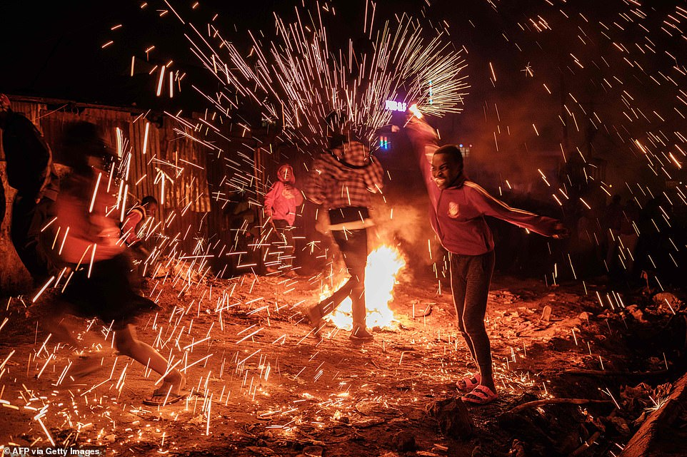 A girl spins a burning steelwool near a bonfire to sprinkle fire sparks as they celebrate the new year on a street of Kibera slum in Nairobi, on January 1, 2020
