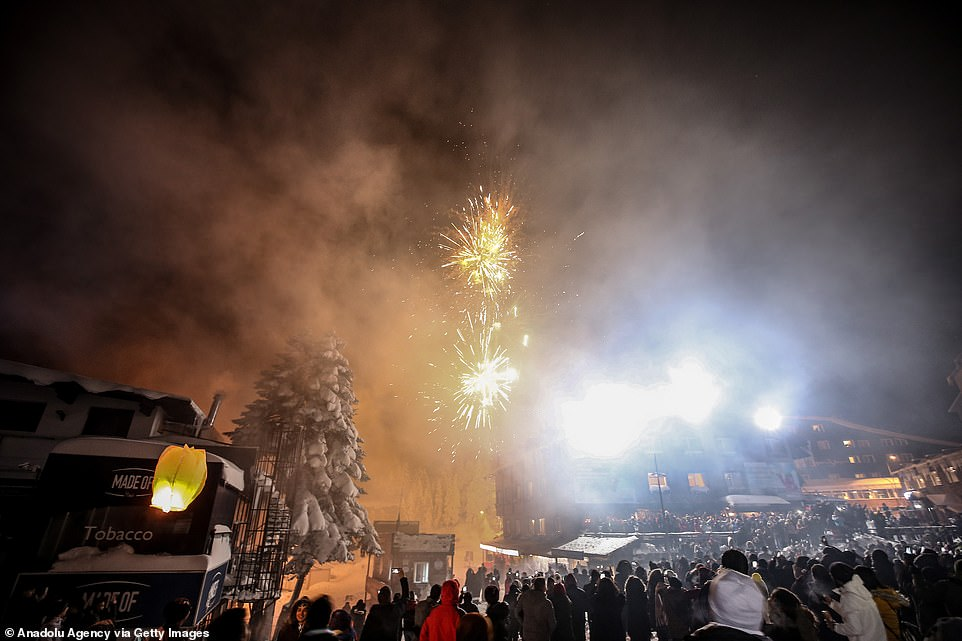 Fireworks go off and illuminate the night sky over people at the Uludag ski resort within the new year celebrations in Bursa, Turkey on January 1, 2020
