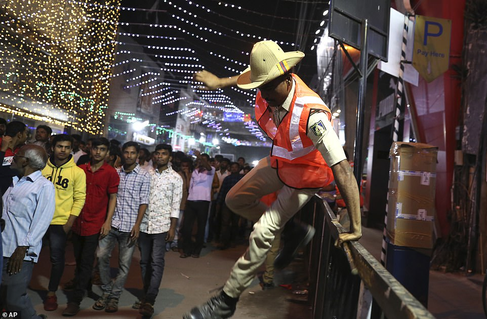A policeman jumps over a railing to manage a crowd of revelers who assembled to celebrate on New Year's eve in Bangalore, India, Tuesday, Dec. 31, 2019